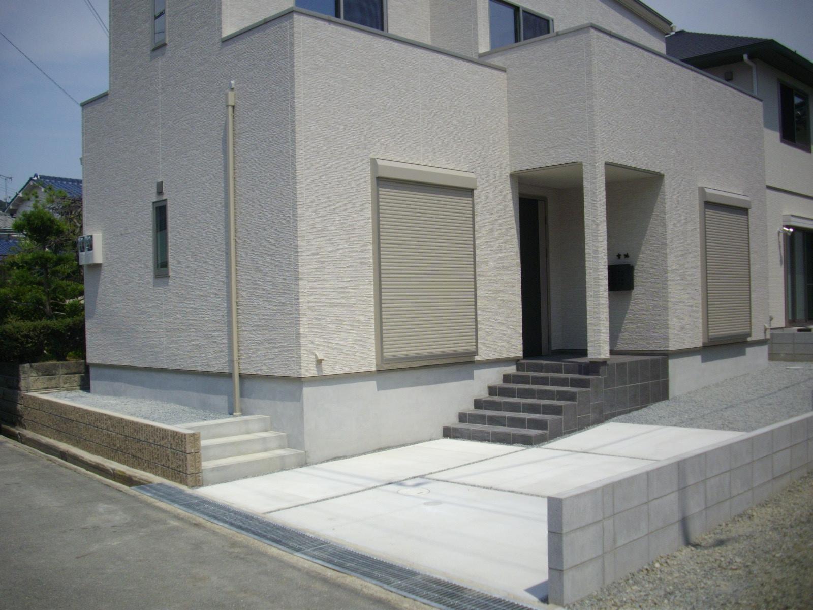白い建物が際立つチャコールグレーのポーチと駐車スペース 加古川 M様邸